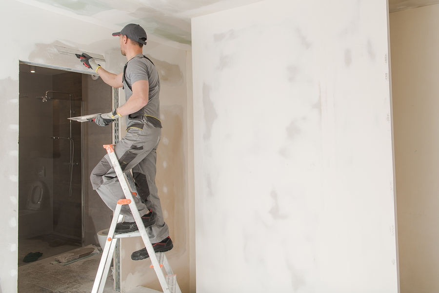 Caucasian Worker in His 30s Patching Drywall Inside Newly Developed House.